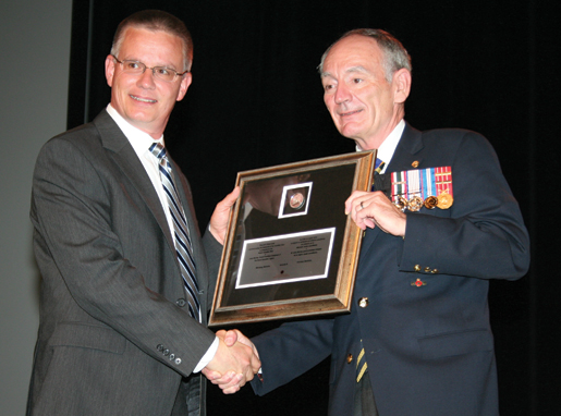 Mark Neuendorff (left), director of the Royal Canadian Mint's Winnipeg facility, presents one of four framed commemorative silver dollars in honour of the navy's centennial to Dominion Grand President Larry Murray. [PHOTO: JENNIFER MORSE]