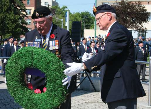 Dominion President Wilf Edmond (left) places a wreath with assistance from Past President Jack Frost. [PHOTO: JENNIFER MORSE]