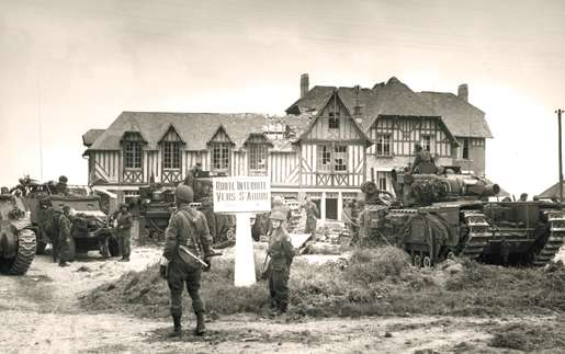 Canadian troops on the outskirts of St. Aubin-sur-Mer on D-Day. [PHOTO:  FRANK L. DUBERVILL, LIBRARY AND ARCHIVES CANADA—PA128789]