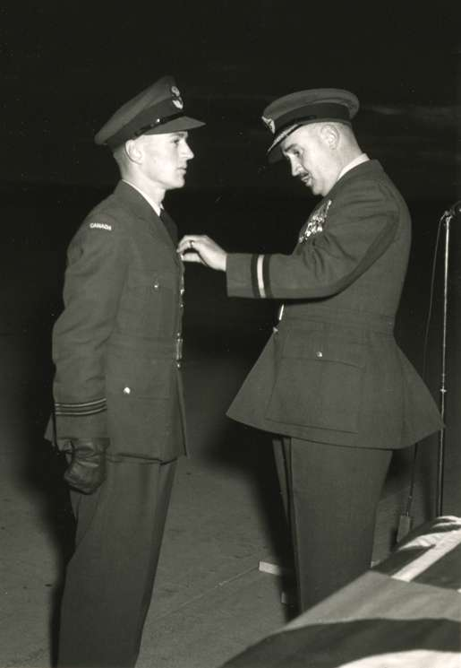 Flying Officer John E. Goldsmith (left) is awarded the Air Force Cross. [PHOTO: CANADIAN FORCES—PL50212]