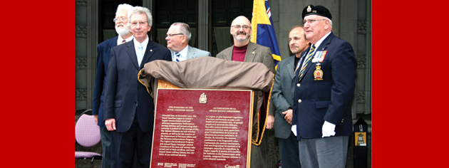 Veterans Affairs Minister Jean-Pierre Blackburn (front left) and Dominion President Wilf Edmond (front right) unveil the plaque recognizing the founding of The Royal Canadian Legion as a historic event. [PHOTO: JENNIFER MORSE]