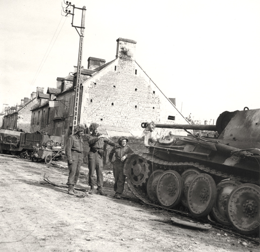 Members of the Regina Rifles examine a destroyed enemy tank, June 8, 1944. [PHOTO: DONALD I. GRANT, LIBRARY AND ARCHIVES CANADA—PA116529]