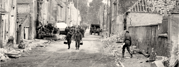 Canadian soldiers move into Bretteville, France, June 20, 1944. [PHOTO: FRANK L. DUBERVILL, LIBRARY AND ARCHIVES CANADA—PA133732]
