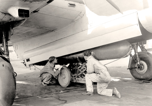 Ground crew load  a torpedo into an aircraft at Patricia Bay, B.C. [PHOTO: LIBRARY AND ARCHIVES CANADA—PA144773]