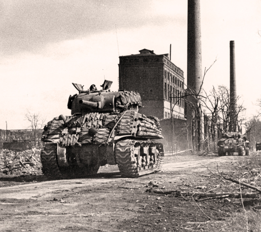 Tanks of the Sherbrooke Fusiliers move up to assist the infantry in clearing a  German town, March 1945. [PHOTO: ERNEST J. DeGUIRE, LIBRARY AND ARCHIVES CANADA—PA192258]