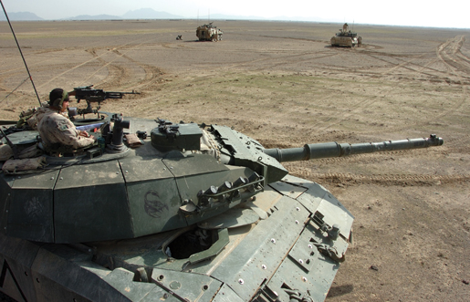 While in the turret of his Leopard tank, a tanker provides security for other armoured vehicles in Kandahar Province, Afghanistan, December 2006. [PHOTO: SERGEANT DENNIS POWER, ARMY NEWS-SHILO]