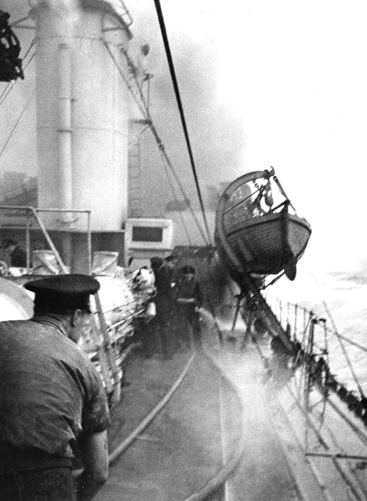 Sailors fight to control a fire on HMCS Assiniboine during the action which resulted in the sinking of U-210. [PHOTO: LIBRARY AND ARCHIVES CANADA—PA184007]