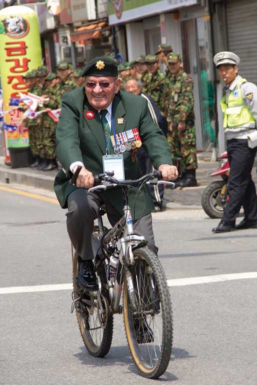 Veteran Guy Vachon of Ottawa rides a bike during the parade at Kapyong. [PHOTO: DAN BLACK]