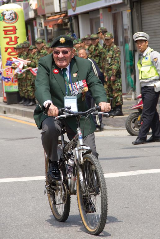 Veteran Guy Vachon of Ottawa rides a bike during the parade at Kapyong. [PHOTO: DAN BLACK]