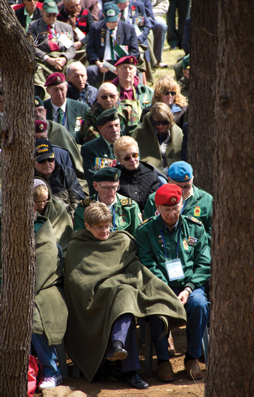 Veterans and their spouses and caregivers cover up during a chilly remembrance service at Gloster Hill. [PHOTO: DAN BLACK]