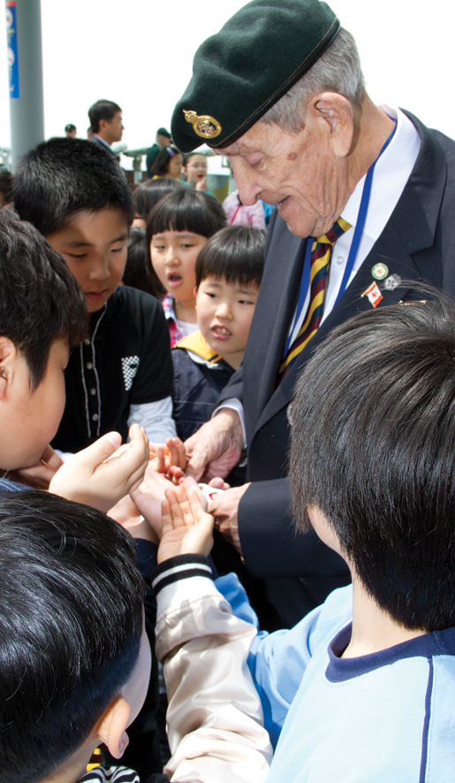 Veteran Donald Doan of Windsor, Ont., hands out souvenirs to schoolchildren. [PHOTO: DAN BLACK]
