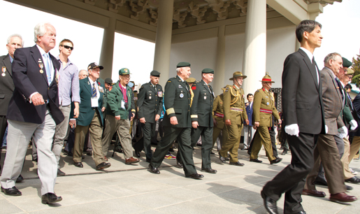 Veterans and dignitaries march toward the memorial in the Korean National Cemetery. [PHOTO: DAN BLACK]