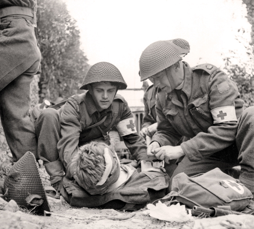 A wounded soldier is treated on the battlefield near Caen, July 15, 1944. [PHOTO: GORDON H. AIKMAN, LIBRARY AND ARCHIVES CANADA—PA133244]