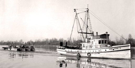 A Fishermen's Naval Reserve vessel hauls in confiscated boats. [PHOTO: LIBRARY AND ARCHIVES CANADA—PA134099]