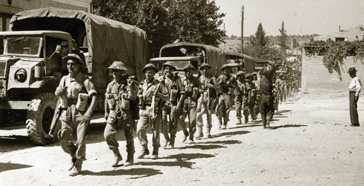 Canadian infantry unit on foot and in convoy passing through an Italian village.