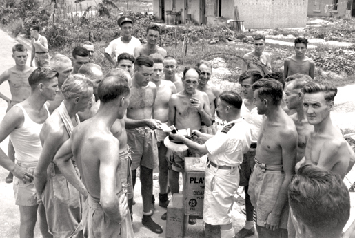 Liberated PoWs gather around for some smokes.  [PHOTO: PO JACK HAWES, LIBRARY AND ARCHIVES CANADA—PA151738]