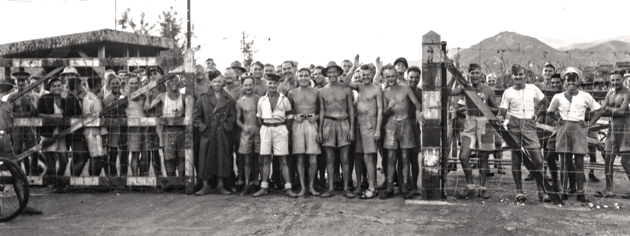 Canadian and British PoWs awaiting liberation by the landing party from HMCS Prince Robert, Hong Kong, August 1945. [PHOTO: PO JACK HAWES, LIBRARY AND ARCHIVES CANADA—PA114811]