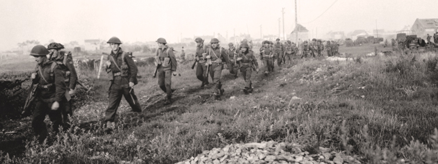Canadian soldiers advance during Operation Spring, July 25, 1944. [PHOTO: KEN BELL, LIBRARY AND ARCHIVES CANADA—PA131378]