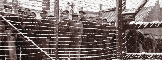 Prisoners look out from behind barbed wire at Sherbrooke, Que., in 1945. [PHOTO: LIBRARY AND ARCHIVES CANADA—PA163788]