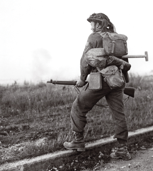A soldier waits for the artillery barrage to clear before moving forward. [PHOTO: KEN BELL, LIBRARY AND ARCHIVES CANADA—PA163403]