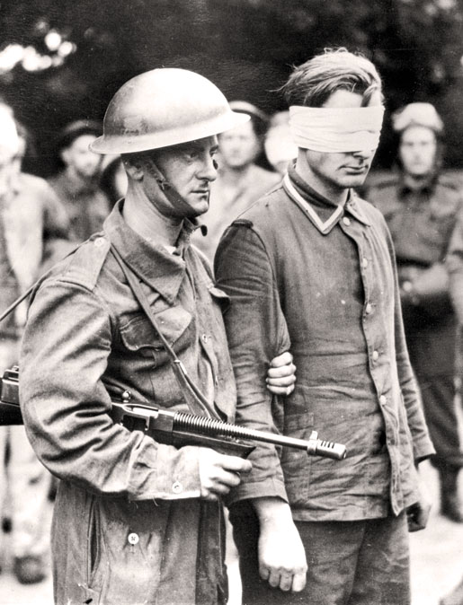 A Canadian escorts a German captured during the raid. [PHOTO: LIBRARY AND ARCHIVES CANADA—PA210156]