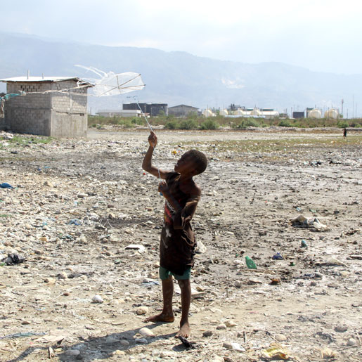 A boy flies a homemade kite in Cité Soleil. [PHOTO: DAN BLACK]