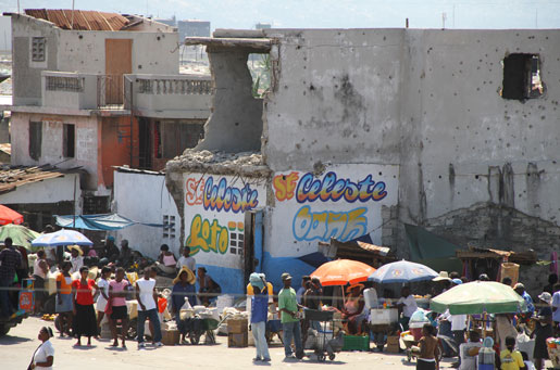 Haitians visit a market outside Cité Soleil. Note the bullet holes on the side of the earthquake-damaged buildings. [PHOTO: DAN BLACK]