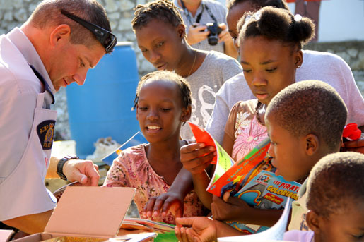 RCMP Staff Sergeant Richard Martel hands out colouring books to children at the orphanage. [PHOTO: DAN BLACK]