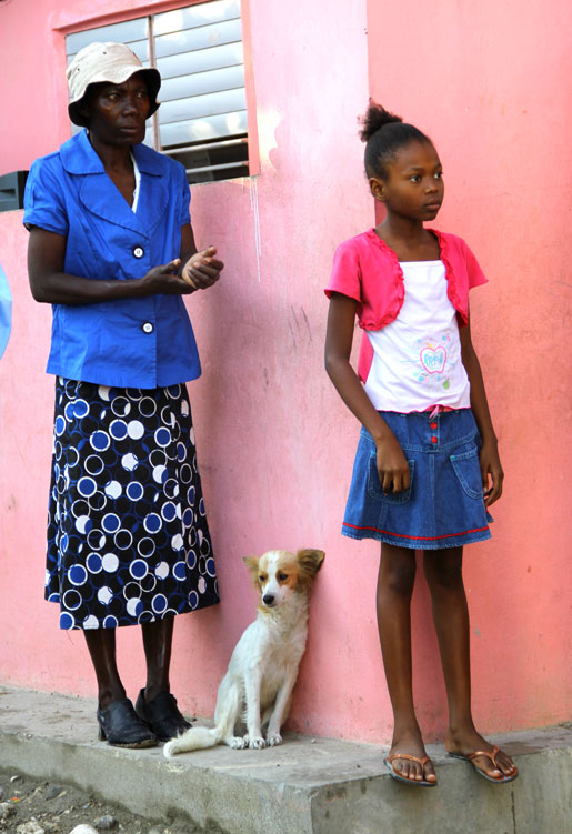 A woman, a girl and dog watch as Canadian visitors learn more about the orphanage. [PHOTO: DAN BLACK]