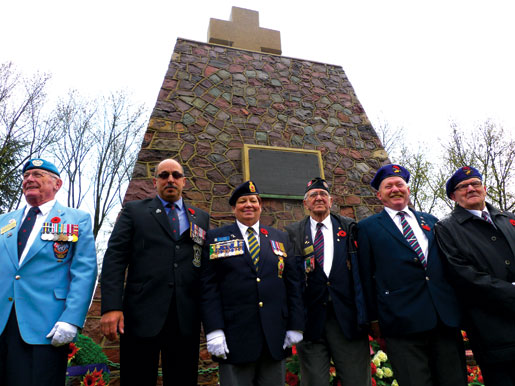 Veterans Robert O'Brien, Reno St-Germain, Dominion President Pat Varga, Neil McKinnon, caretaker Edward Corbett and Gene Heesaker at the memorial in Thélus.