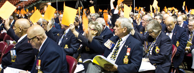 Delegates raise cards to vote on resolutions. [PHOTO: DAN BLACK]