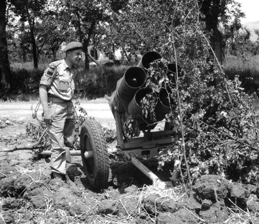 Lieutenant W.H. Salter examines a loaded Nebelwerfer, 1944. [PHOTO: STRATHY E. SMITH, LIBRARY AND ARCHIVES CANADA—PA169113]