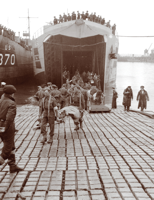 Canadian soldiers wounded on the Normandy beachhead are carried off a Landing Ship Tank in Southampton, England, June 1944. [PHOTO: LT. MICHAEL M. DEAN, LIBRARY AND ARCHIVES CANADA—PA131437]