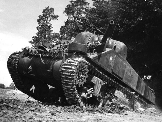 A Canadian Sherman tank rolls over a rise on the Normandy battlefield, 1944. [PHOTO: LEGION MAGAZINE ARCHIVES]