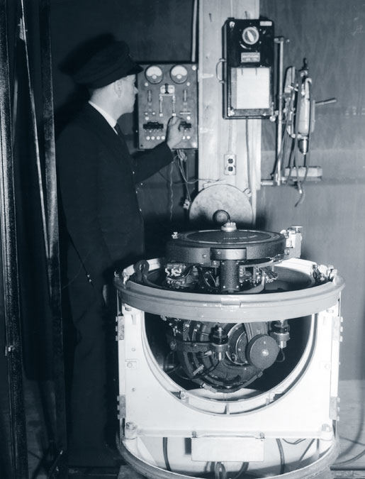 A Gyro compass undergoes repair at HMC Dockyard, February 1943. [PHOTO: JACKSON GEORGE KEMPSTER, LIBRARY AND ARCHIVES CANADA—PA106969]