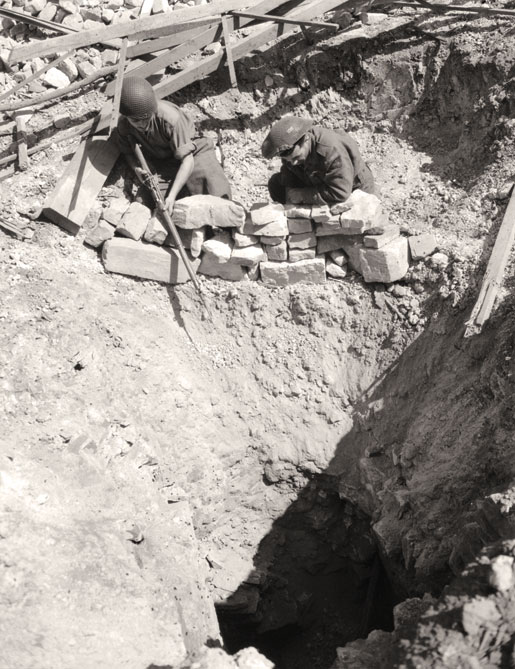 Members of Les Fusiliers Mont-Royal peer into a mine shaft used by German troops for infiltration purposes, August 1944. [PHOTO: KEN BELL, LIBRARY AND ARCHIVES CANADA—PA131353]