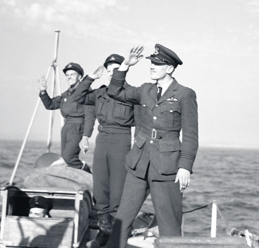 Squadron Leader Wally McLeod and two other pilots salute sailors as they pull away from HMS Rodney in 1944. The airmen visited the ship during some free time from operations in Normandy. [PHOTO: CANADIAN FORCES JOINT IMAGERY CENTRE—PL30668]