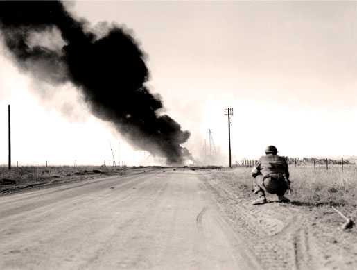 Smoke from burning vehicles blackens the sky above the Caen-Falaise Road near Hautmesnil, France, August 1944. [PHOTO: DONALD GRANT, LIBRARY AND ARCHIVES CANADA—PA191881]