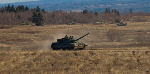 Tanks and LAV IIIs charge out of gullies during exercises at Canadian Forces Base Gagetown. [PHOTO: TOM MacGREGOR]