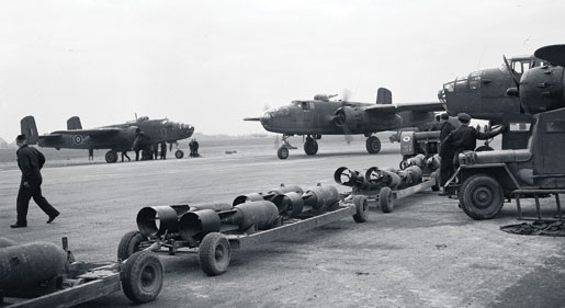 A fresh supply of bombs awaits incoming Mitchell bombers, March 1945. Fuelling and bomb-loading operations sometimes began even before crews alighted from the aircraft. [PHOTO: CANADIAN FORCES JOINT IMAGERY CENTRE—PL42718]