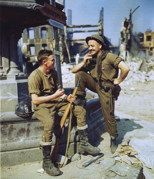 Two privates relax in a square in Falaise. [PHOTO: LIBRARY AND ARCHIVES CANADA—E010786190]