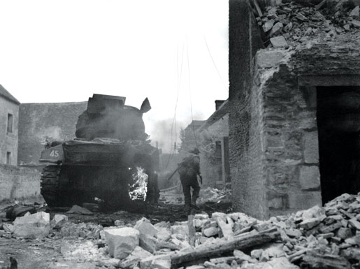 A tank burns while a Canadian picks his way through St. Lambert-sur-Dives. [PHOTO: DONALD I. GRANT, LIBRARY AND ARCHIVES CANADA—PA132192]