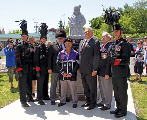 Mohawk Branch President Louis Stacey (centre) stands with members of the Voltiguers in front of the monument. [PHOTO: TOM MACGREGOR]