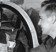 Flight Lieutenant Ernie Glover shakes hands with another airman while seated in his Canadian-built Sabre. [PHOTO: ROYAL CANADIAN AIR FORCE]