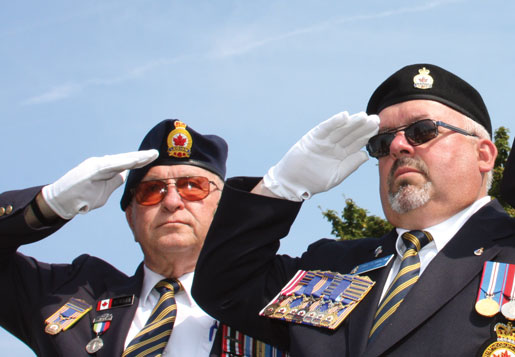 Sam Newman and Legion Dominion Vice-President Dave Flannigan salute at Tyne Cot Cemetery. [PHOTO: SHARON ADAMS]