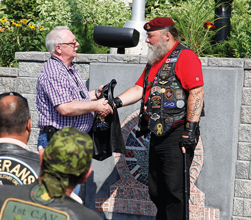 Dominion President Gordon Moore (left) presents a Legion Riders vest to CAV founder Paul Cane. [PHOTO: ADAM DAY]