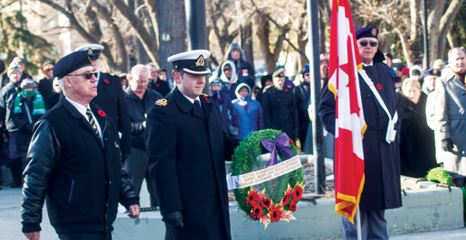 Regina Branch First Vice Ian Brown places a wreath on behalf of veterans groups, including the Legion. [PHOTO: TOM MacGREGOR]