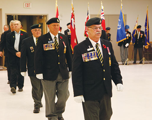 Dominion representative Paul Poirier leads Manitoba-Northwestern Ontario Command Past President Rick Bennett (second from right) and other guests towards the stage. [PHOTO: ADAM DAY]
