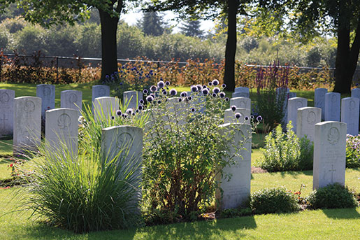 Canadian graves flank carefully tended flowers in Groesbeek Canadian War Cemetery near Nijmegen, Netherlands. [PHOTO: SHARON ADAMS, LEGION MAGAZINE]