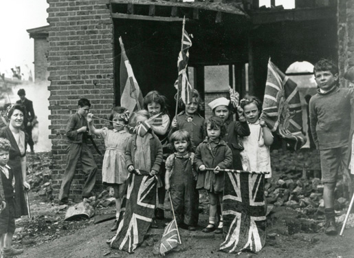Young children in bomb scarred Battersea in south London with their Union flags. [PHOTO: LEGION MAGAZINE ARCHIVES]
